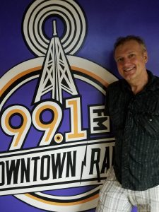Jason LeValley by the Downtown Radio Logo Mural